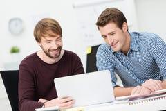 Två lyckliga affärsmän som tillsammans arbetar royaltyfria bilder