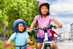 Två lyckliga afrikanska flickor som rider cyklar i stad Royaltyfria Foton