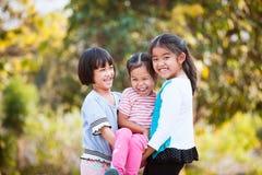 Två lyckliga asiatiska barn som bär hennes syster arkivbild