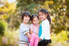 Två lyckliga asiatiska barn som bär hennes syster Arkivfoton