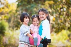 Två lyckliga asiatiska barn som bär hennes syster Fotografering för Bildbyråer