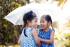 Två lyckliga asiatiska små flickor med paraplyet Arkivfoton