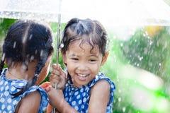 Två lyckliga asiatiska små flickor med paraplyet Royaltyfri Foto