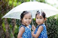 Två lyckliga asiatiska små flickor med paraplyet Royaltyfri Bild