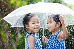 Två lyckliga asiatiska små flickor med paraplyet Arkivfoto