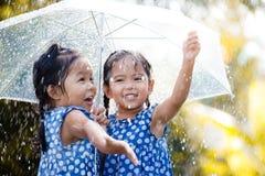 Två lyckliga asiatiska små flickor med paraplyet Arkivbilder