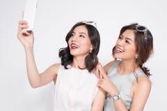 Två lyckliga asiatiska unga kvinnor med smartphonen som tar selfie arkivfoto