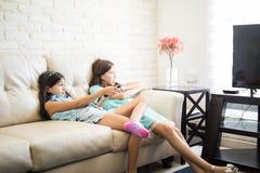 Två lyckliga attraktiva systrar eller flickavänner på soffan på hom Arkivfoton