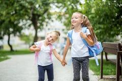 Två lyckliga barn går till skolan Begreppet av skolan, studie, utbildning, kamratskap, barndom fotografering för bildbyråer