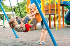 Två lyckliga barn på lekplatsen Royaltyfri Bild