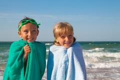 Två lyckliga barn på stranden, hav i bakgrund royaltyfri bild