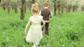 Två lyckliga barn pojke och flickaspring runt om blomningen arbeta i trädgården i ultrarapid arkivfilmer