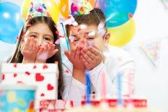 Två lyckliga barn som har gyckel på födelsedagpartiet arkivfoto