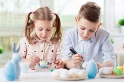 Två lyckliga barn som har gyckel under målningägg för easter in arkivfoto
