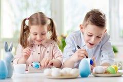 Två lyckliga barn som har gyckel under målningägg för easter in arkivfoton