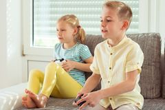 Två lyckliga barn som hemma spelar videospel fotografering för bildbyråer