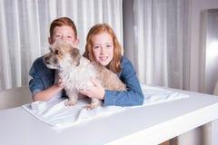 Två lyckliga barn som kramar deras lilla hund Arkivfoton