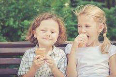 Två lyckliga barn som spelar i parkera på dagtiden Arkivfoto