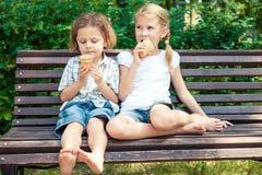 Två lyckliga barn som spelar i parkera på dagtiden Fotografering för Bildbyråer