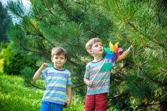 Två lyckliga barn som spelar i trädgård med väderkvarnlilla solen Förtjusande siblingbröder är bästa vän Gullig vår för ungepojke arkivfoton