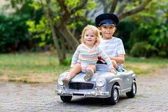 Två lyckliga barn som spelar med den stora gamla leksakbilen i sommarträdgård, utomhus Lura pojken som kör bilen med den lilla li royaltyfri bild