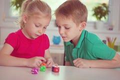 Två lyckliga barn som spelar med, tärnar arkivbilder