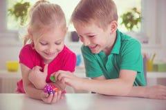 Två lyckliga barn som spelar med, tärnar royaltyfri foto