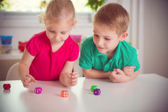 Två lyckliga barn som spelar med, tärnar royaltyfria bilder