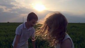 Två lyckliga barn som spelar på ängen, solnedgång stock video