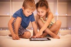 Två lyckliga barn som spelar på minnestavlan royaltyfria foton