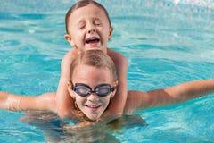 Två lyckliga barn som spelar på simbassängen på dagtiden Royaltyfri Bild