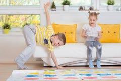 Två lyckliga barn som spelar spännande modigt hemmastatt arkivbilder