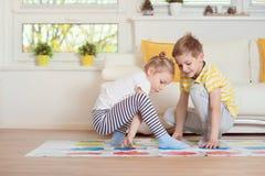 Två lyckliga barn som spelar spännande modigt hemmastatt royaltyfri foto