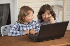 Två lyckliga barn som utomhus spelar med bärbara datorn royaltyfri fotografi