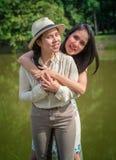 Två lyckliga damer framme dammet royaltyfri bild