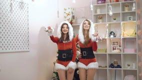 Två lyckliga damer som dansar och att le med julleksaker i 4K lager videofilmer