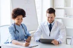 Två lyckliga doktorer som möter på sjukhuskontoret royaltyfri bild
