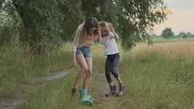 Två lyckliga flickasystrar som går efter regn i smutsiga kläderbarn som talar att skratta, roligt hällande vatten från deras käng arkivfilmer