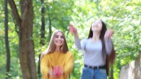 Två lyckliga flickavänner med långt hår som kastas upp röda roskronblad lager videofilmer