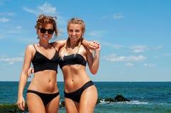 Två lyckliga flickor i bikini på stranden Bästa vän som har gyckel, livsstil för ferie för sommarsemester arkivfoton