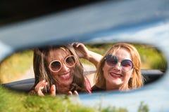 Två lyckliga flickor i en bilbackspegel Fotografering för Bildbyråer