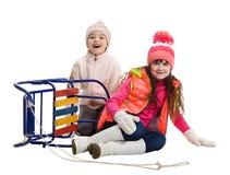 Två lyckliga flickor i vinterkläder bredvid släden Arkivbild