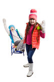 Två lyckliga flickor i vinterkläder på släden Royaltyfri Fotografi