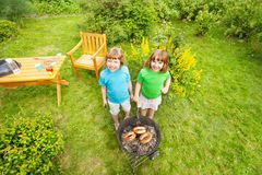Två lyckliga flickor near BBQ som utanför grillar kött Royaltyfria Foton