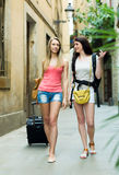 Två lyckliga flickor på semestern som heading till hotellet Arkivbild