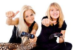 Två lyckliga flickor play videospel royaltyfria foton