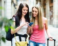 Två lyckliga flickor som finner banan med GPS navigatören Royaltyfri Fotografi