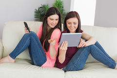 Två lyckliga flickor som sitter på en soffa genom att använda minnestavlaPC och mobil pho royaltyfri foto