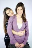 Två lyckliga flickvänner kramat le Arkivbild