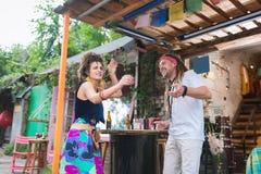 Två lyckliga flower-power-folket som dansar, medan kyla i bar arkivbild